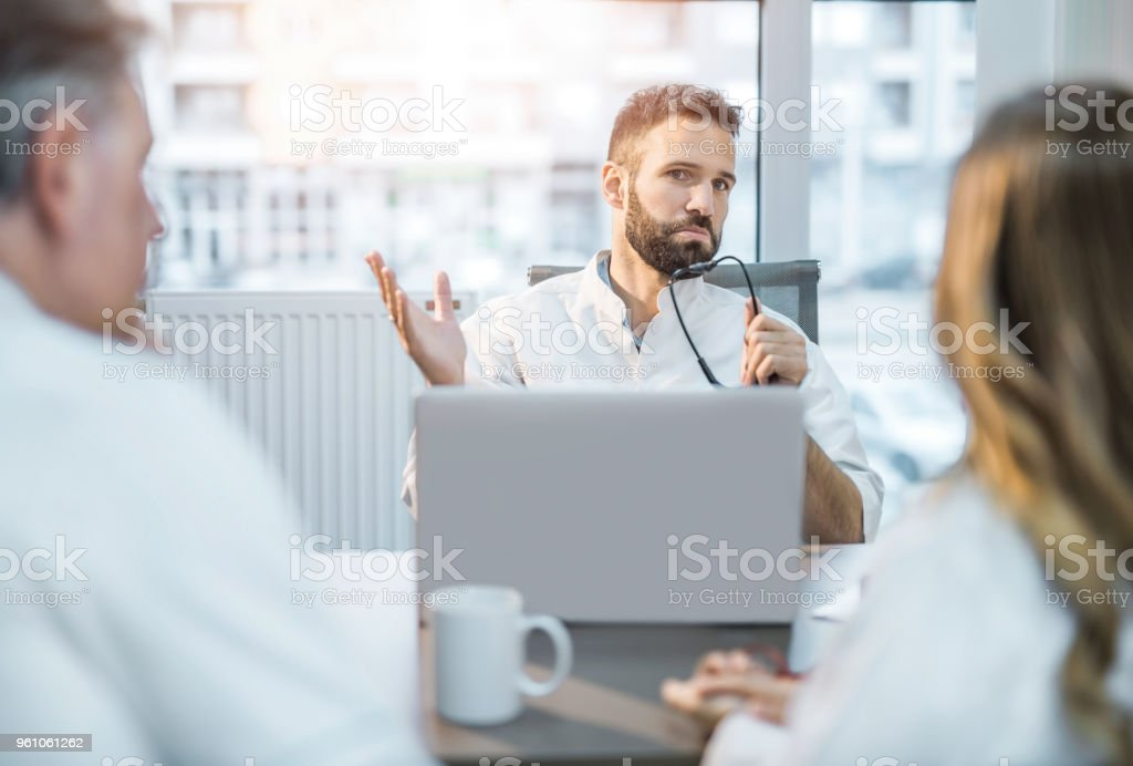 Male mid adult doctor having a discussion with his colleagues. stock photo