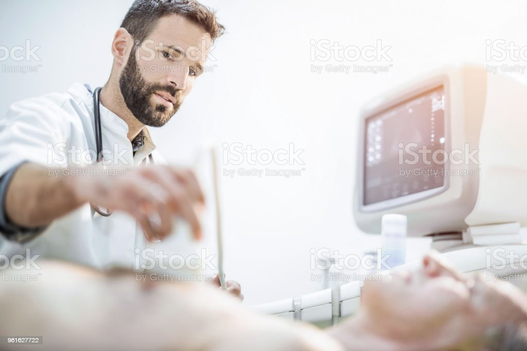 Male mid adult healthcare worker examining senior patient's chest with ultrasound. stock photo