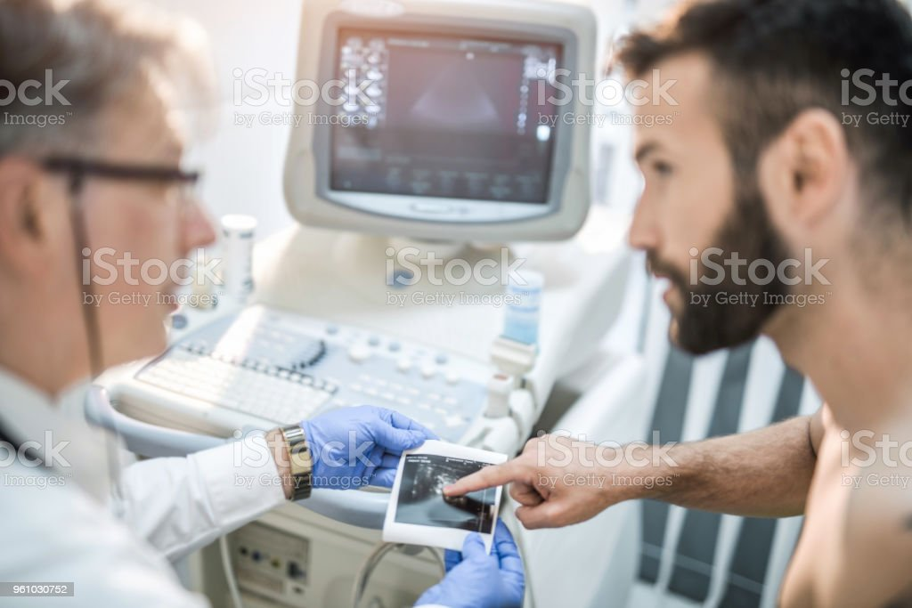 Male mid adult patient and mature doctor looking at ultrasound image results. stock photo