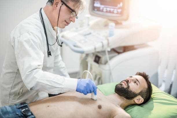 male mid adult patient on ultrasound. - cardiologist stock pictures, royalty-free photos & images