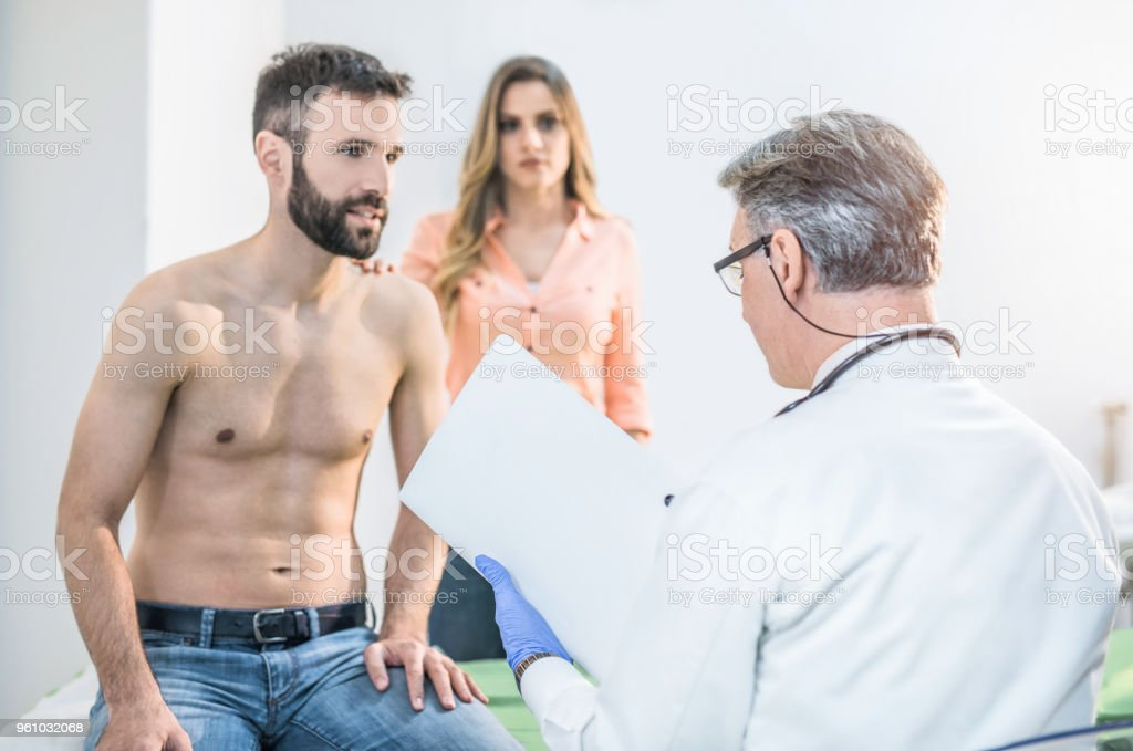 Male mid adult patient with his supportive wife waiting for medical test results. stock photo