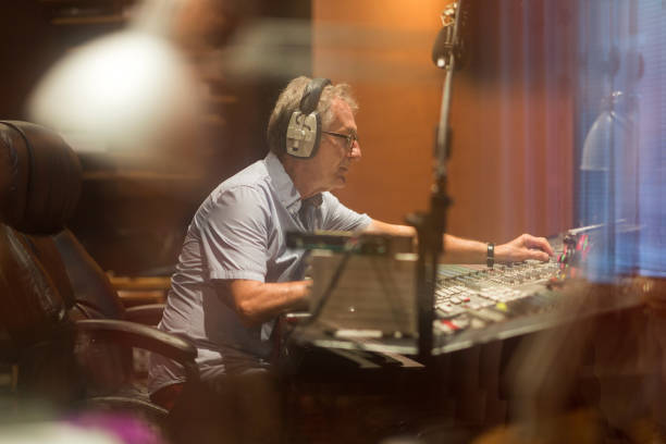 Male middle aged recording engineer in a recording studio sitting at a multi channel console Male middle aged recording engineer in a recording studio sitting at a multi channel console radio dj stock pictures, royalty-free photos & images