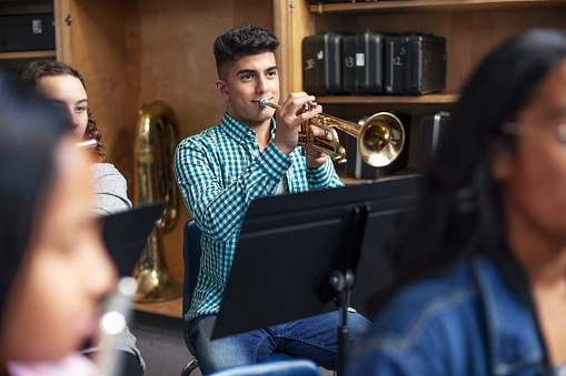Confident male student playing trumpet in musical class. Aspiring teenage boy is learning wind instrument. He is practicing with friends in high school.