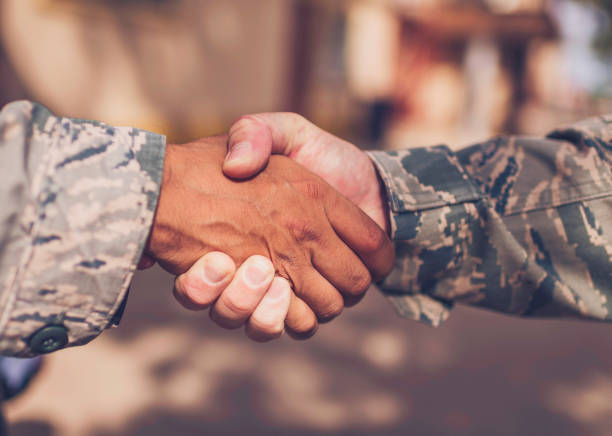 Male military soldiers shaking hands stock photo