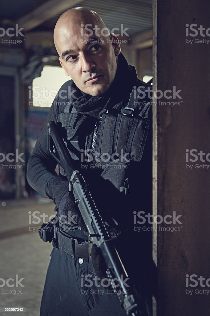 Male military swat team member holding gun in abandoned warehouse stock photo