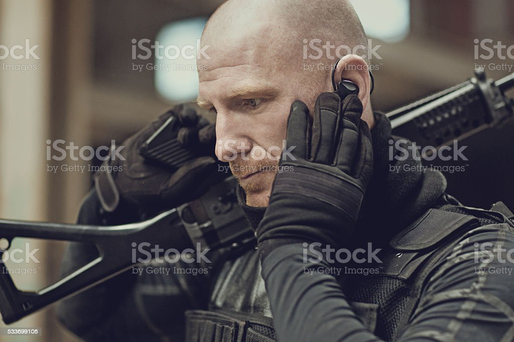 Male military swat team member holding rifle in abandoned warehouse stock photo