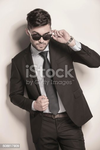 907934274 istock photo male model in suit and tie taking off his sunglasses 508817909