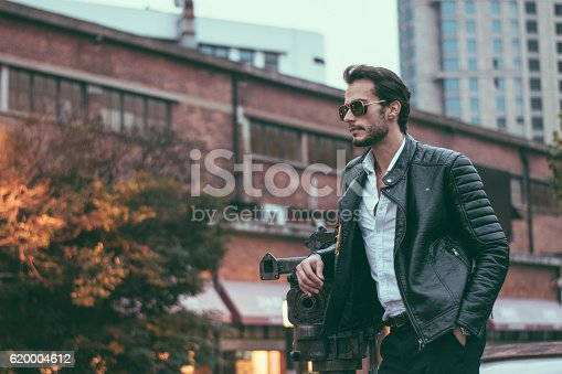Young handsome man standing by the recording camera made of steel, outdoors in the city,