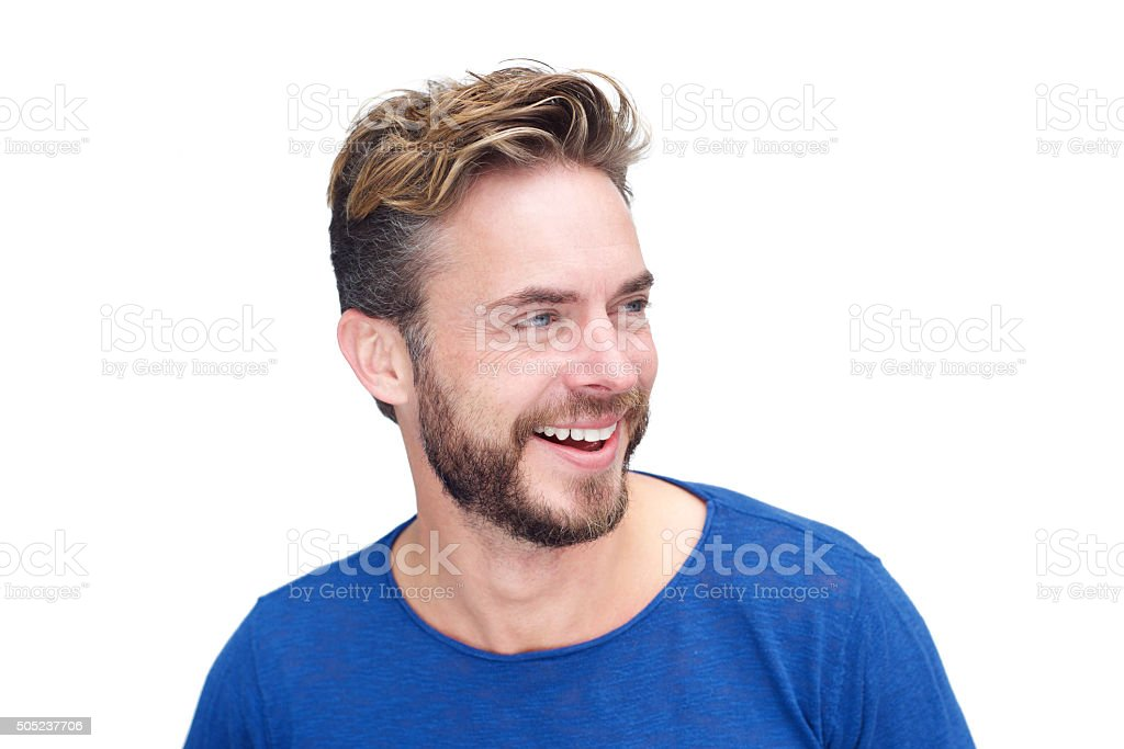 Close up portrait of a male model with beard laughing against white...