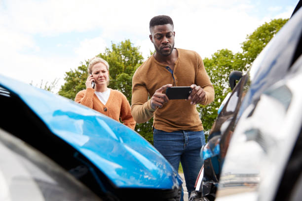male motorist involved in car accident taking picture of damage for insurance claim - car photos stock pictures, royalty-free photos & images