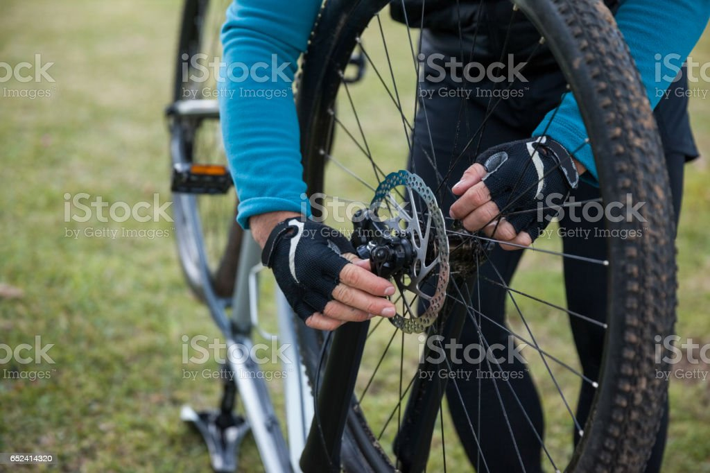 Male mountain biker examining front wheel of his bicycle stock photo