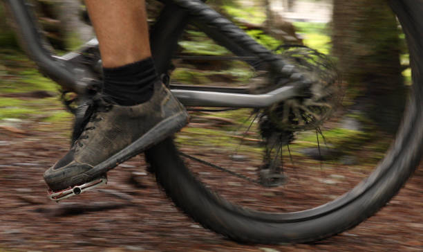 male mountain biker follows trail through forest - men shoes stock pictures, royalty-free photos & images