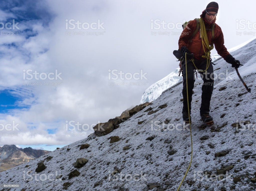 male mountain climber coming down from a high peak in the Andes in Peru stock photo
