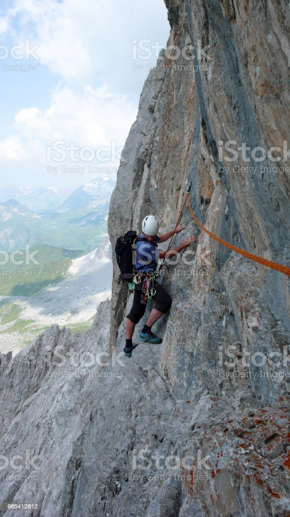 male mountain climber on a steep rock climbing route in the Swiss Alps near Klosters royalty-free stock photo