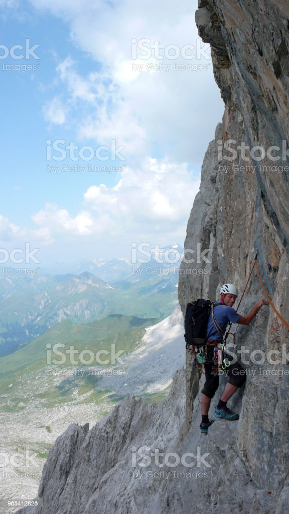 male mountain climber on a steep rock climbing route in the Swiss Alps near Klosters zbiór zdjęć royalty-free