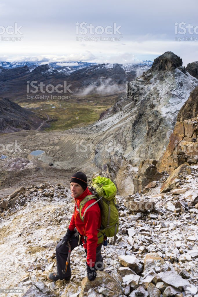male mountain climber on a steep rock slope on his way to the summit stock photo