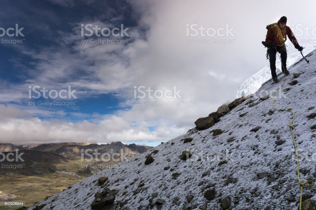 male mountain climber on a steep rocky slope in the Cordillera Blanca in Peru stock photo