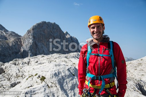 Mid-adult man in mountain climbing gear standing high mountains with a smile on his face. Evening mood.