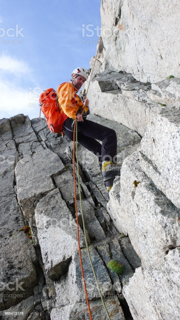 male mountain climber rappelling off a steep rocky ridge in the French Alps near Chamonix royalty-free stock photo