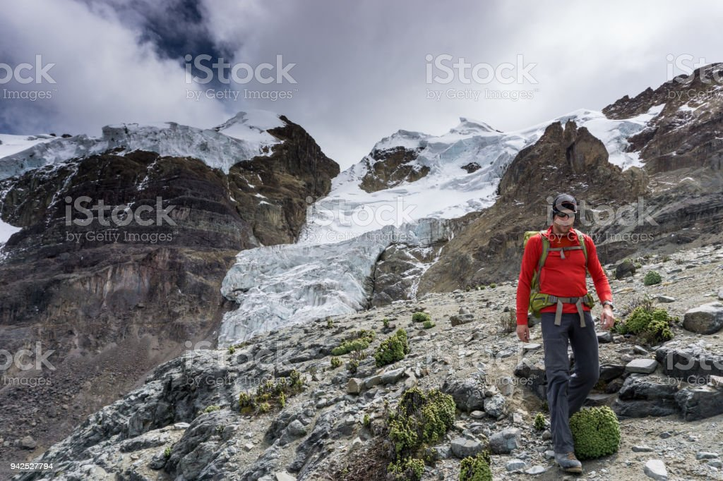 male mountain climber returns to base camp after climbing a high peak in the Andes in Peru stock photo