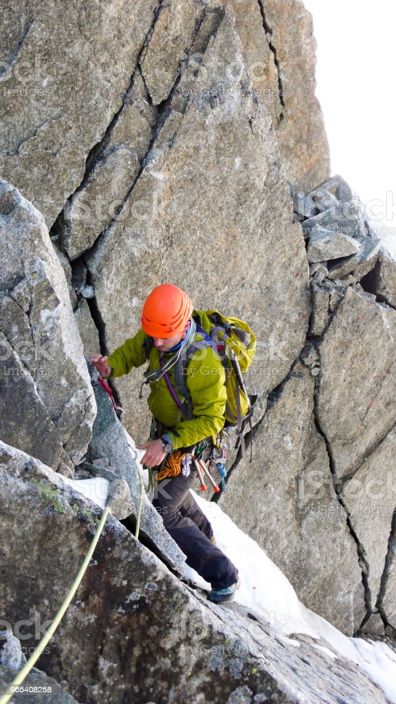 male mountain climber traverses a tricky rock chimney on his way to a high alpine summit royalty-free stock photo
