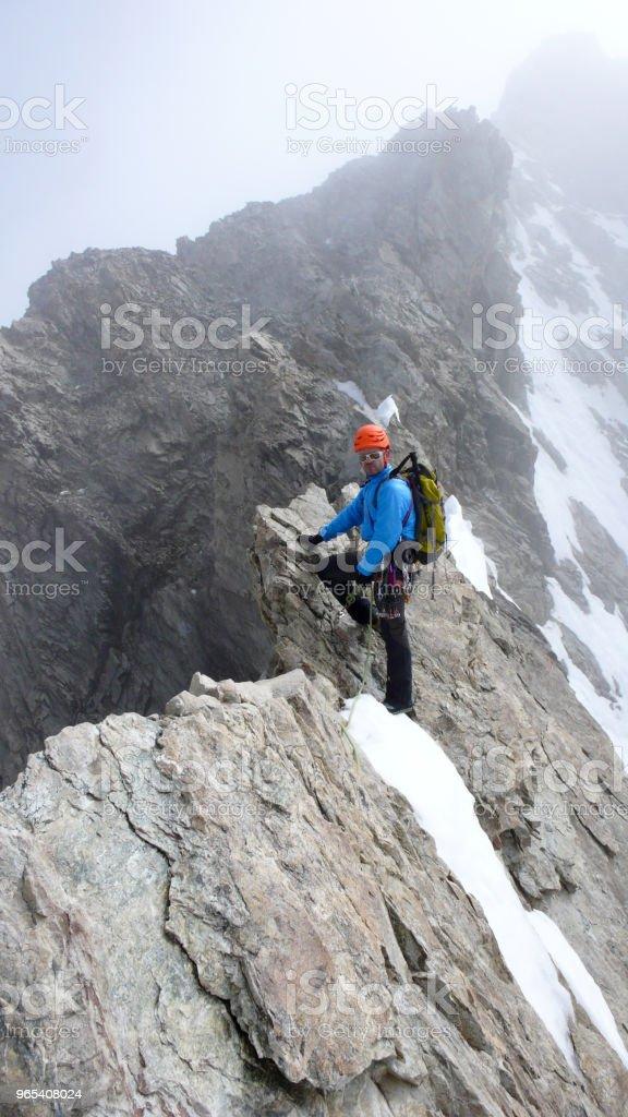 plomb de guide de montagne mâle grimpant sur une crête de granit apparentes dans les Alpes - Photo de Adulte libre de droits