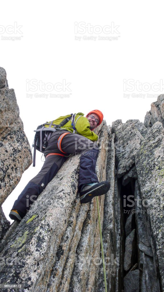 male mountain guide lead climbing on an exposed granite ridge in the Alps royalty-free stock photo