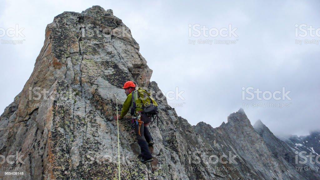 male mountain guide lead climbing on an exposed granite ridge in the Alps zbiór zdjęć royalty-free