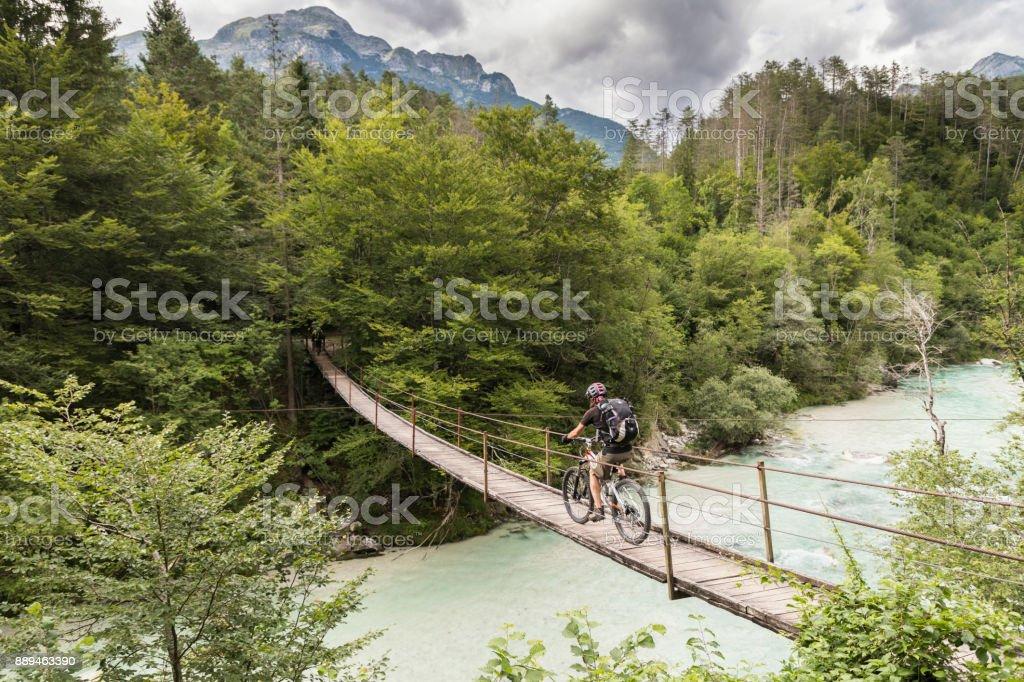 Male mountainbiker is crossing a suspension bridge in Slovenia. stock photo