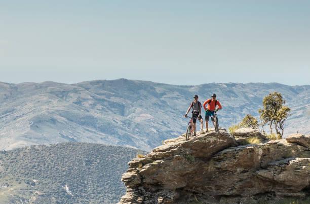 Männliche Mountainbiker posiert auf einem Felsen in der andalusischen Sierra Nevada. – Foto