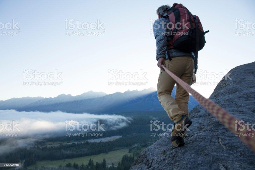 Male mountaineer traverses mountain ridge at sunrise canadian rockies stock photo