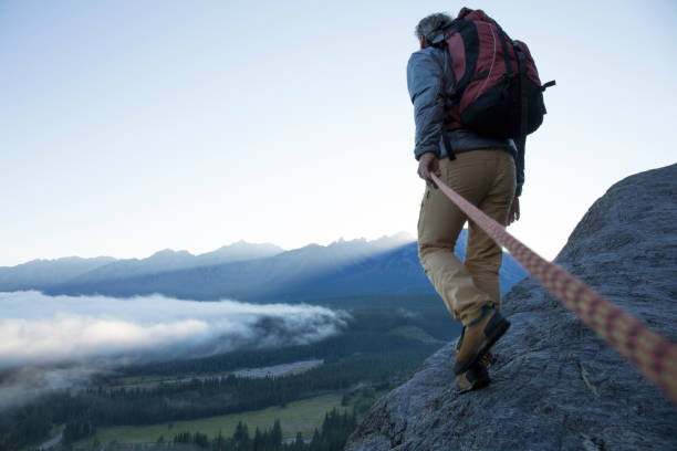 male mountaineer traverses mountain ridge at sunrise canadian rockies - dedication stock photos and pictures