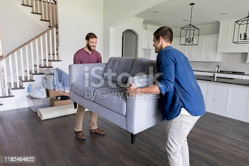 Young men work together to carry a sofa into a new home.
