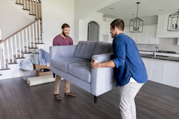 Male movers carry sofa into home Young men work together to carry a sofa into a new home. physical activity stock pictures, royalty-free photos & images