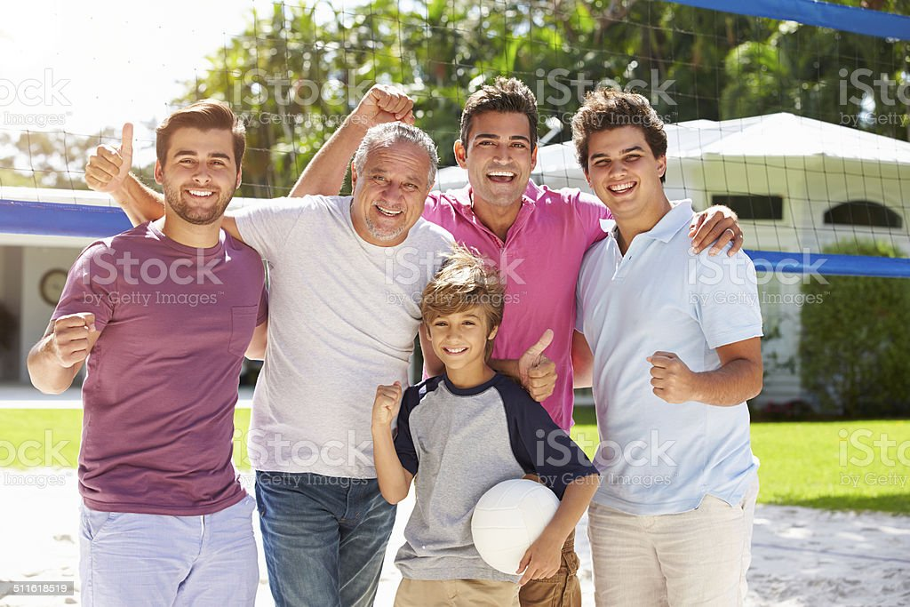 Male Multi Generation Family Playing Volleyball In Garden stock photo