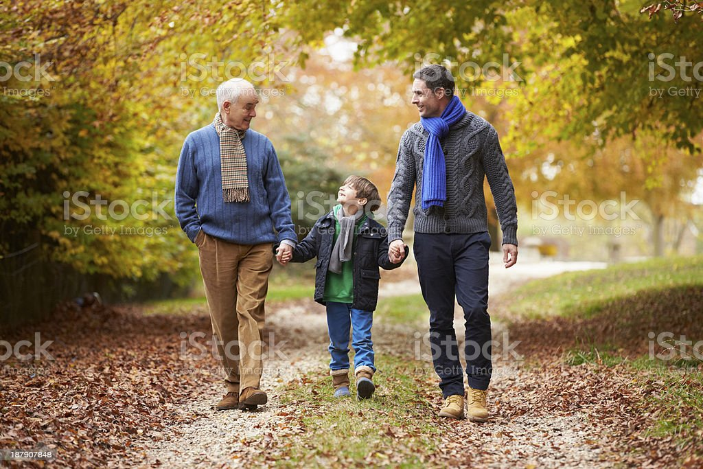 Male Multl Generation Family Walking Along Autumn Path stock photo