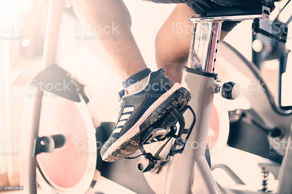 Male muscular exercising on a exercise bike in gym stock photo