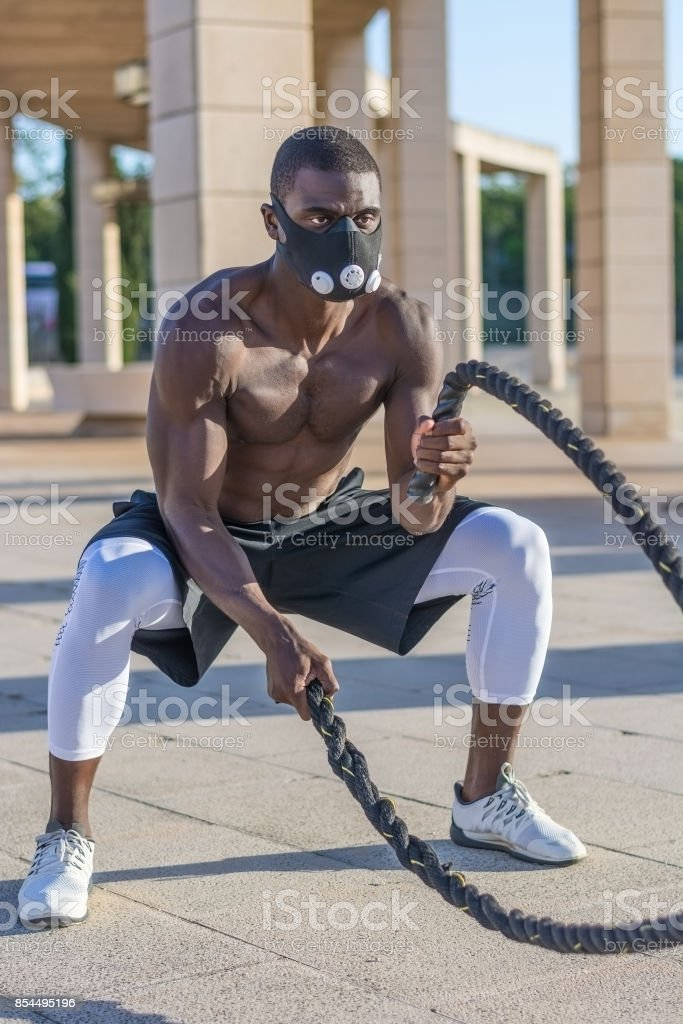 male muscular training with battle ropes and training mask stock photo