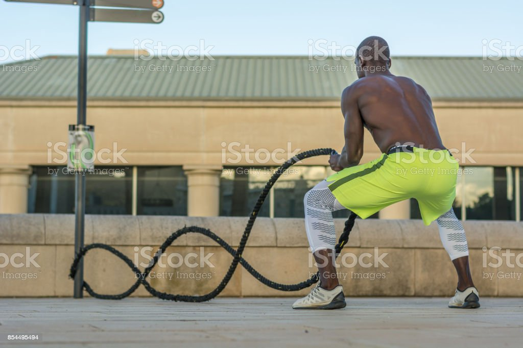 male muscular training with battle ropes stock photo