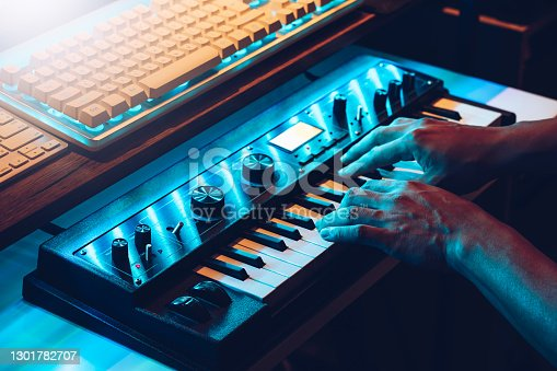 male musician hands playing on synthesizer keys. music concept