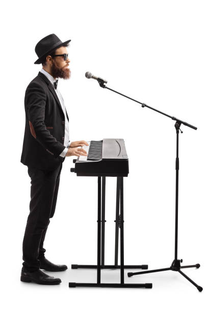 Male musician playing a digital piano and singing on a microphone Full length profile shot of a male musician playing a digital piano and singing on a microphone isolated on white background keyboard player stock pictures, royalty-free photos & images