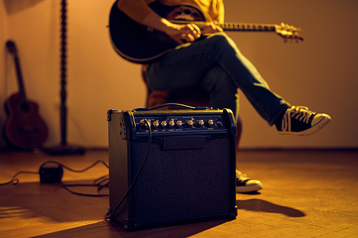 Male musician playing acoustic guitar on the amplifier in retro vintage room.