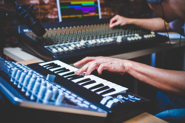 male musician playing midi keyboard synthesizer in recording studio, focus on hands male musician playing midi keyboard synthesizer in recording studio, focus on hands producer stock pictures, royalty-free photos & images
