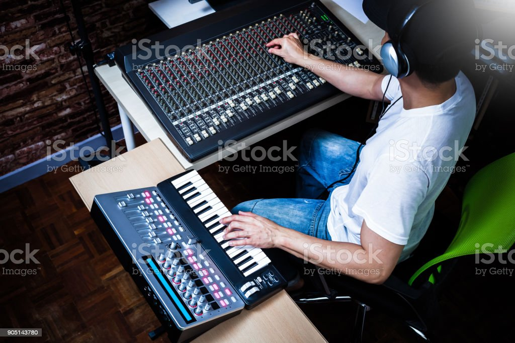 male musician playing midi keyboard synthesizer in recording studio, focus on hands stock photo