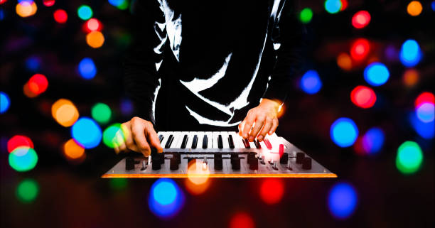 male musician, remixer, dj playing music keyboard synthesizer with colourful bokeh male musician, remixer, dj playing music keyboard synthesizer with colourful bokeh electronic music stock pictures, royalty-free photos & images