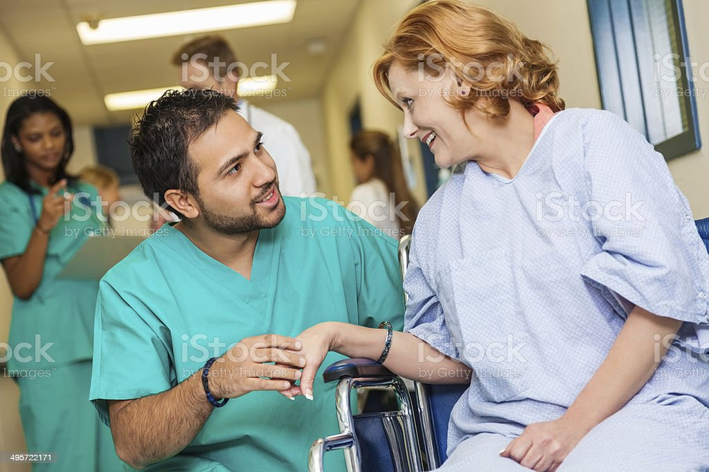 Male nurse assisting female patient in wheelchair at hospital stock photo