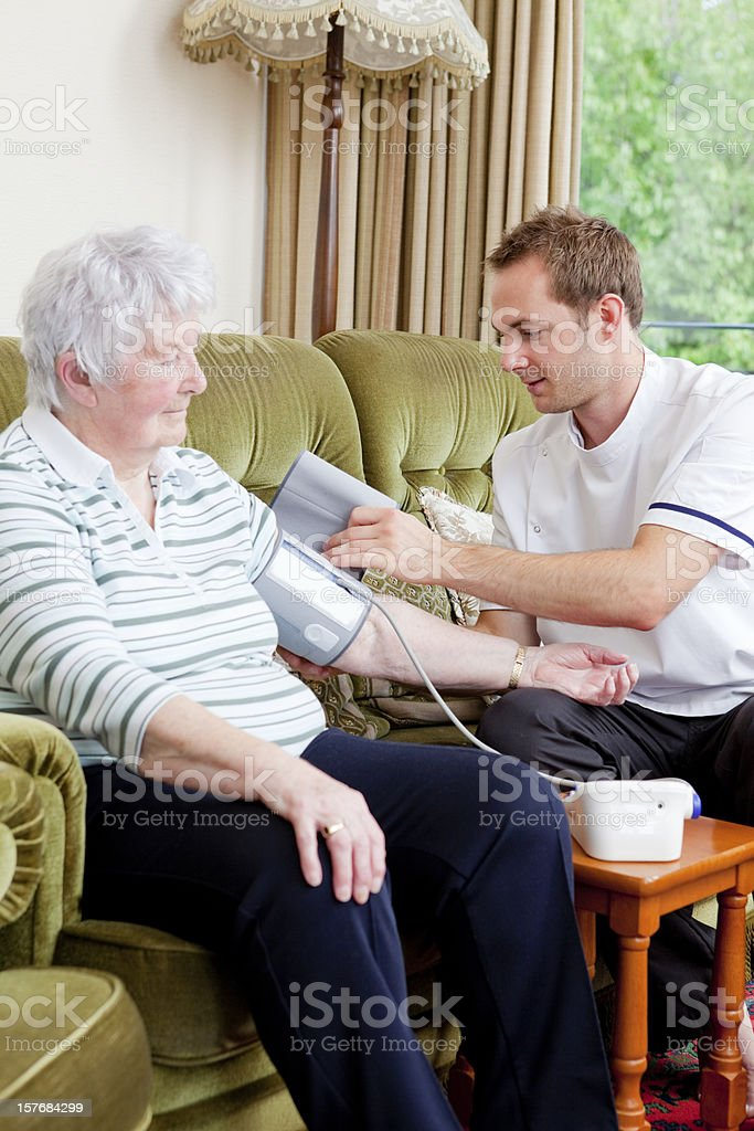 Young male nurse checking senior ladys blood pressure in a care home.