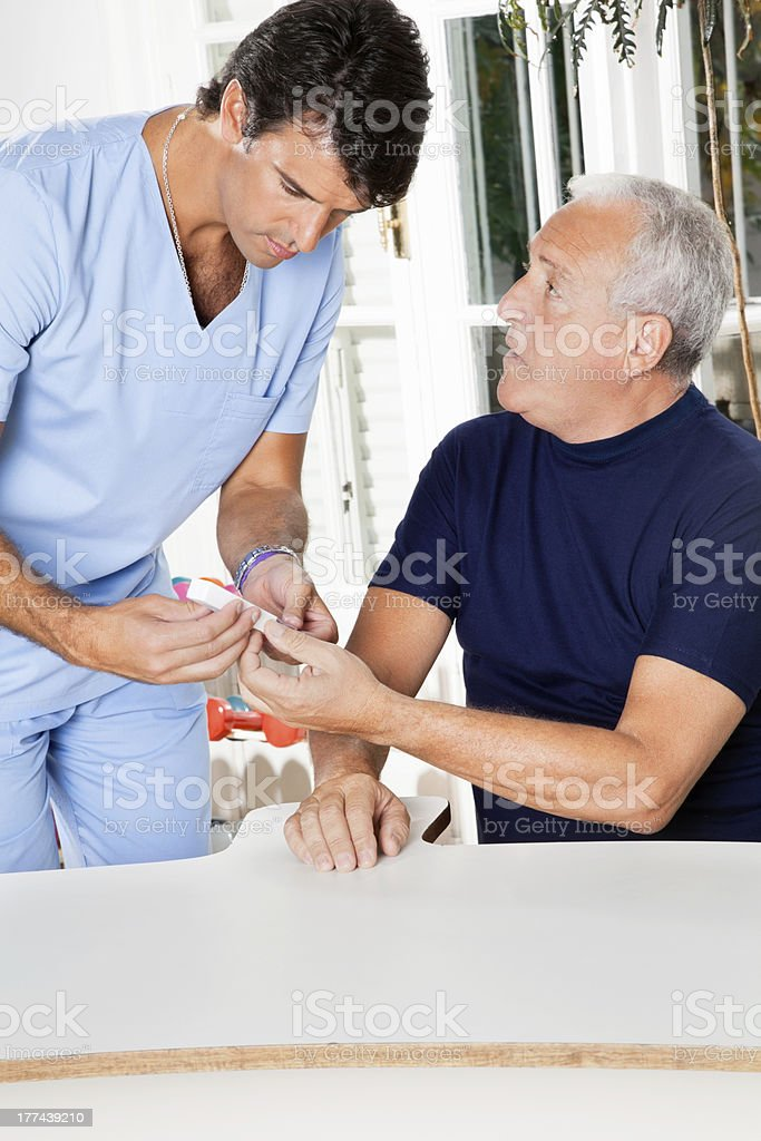 Male Nurse Checking Sugar Level Of Senior Man stock photo