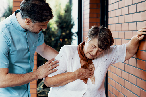 istock Male nurse helping sick elderly woman with chest pain 1147153827