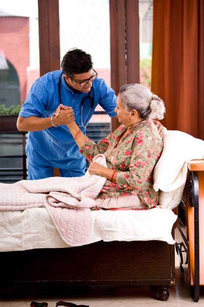 Männliche Krankenschwester zu Hause Betreuer hilft Seniorin entspannen auf dem Bett – Foto